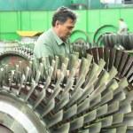 Постер, плакат: Mechanic works with part of aviation engine