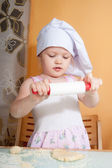 Baby girl in cook role on kitchen — Stock Photo