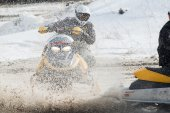 Snowmobile moves on bend of sport track — Stock Photo