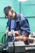 Senior worker grinds detail — Fotografia Stock