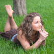 Attractive girl relaxes on grass — Stock Photo #56364717