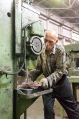 Elderly worker drills bores on detail by driller — Stock Photo