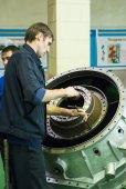 Mechanic assembles part for aviation engine — Stock Photo