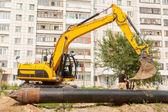 Using of excavator as crane for raising of pile — Stock Photo