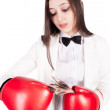 Young businesswoman in boxing gloves with cash — Stock Photo #62416407