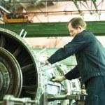 Постер, плакат: Elderly mechanic assembles aviation engine