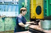 Senior woman stamps details on hydraulic press — Stock Photo
