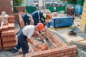 Team of bricklayers on house construction — Stock Photo