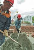 Workers knead solution for bricklayers — Stock Photo