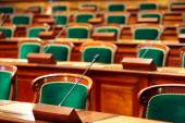 Empty vintage congress hall with seats and microphones. — Stock Photo