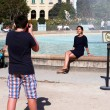 Teenage boy photographing girl, that sitting on the fountain — Stock Photo #57331353