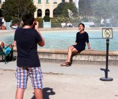 Teenage boy photographing girl, that sitting on the fountain — Stock Photo