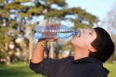 A boy thirsty eagerly drinking water from plastic bottle — Stock Photo
