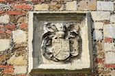 Heraldic stone carving set in wall — Stock Photo