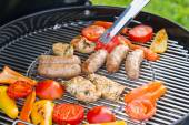 Sausages, meat and vegetables on a grill — Stock Photo