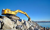 Excavator on large rocks on the beach — ストック写真