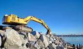 Excavator on large rocks on the beach — Fotografia Stock