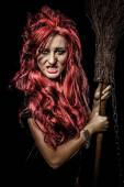 Evil red-haired witch and her broomstick — Stock Photo
