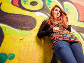 Redhead woman with earphones at graffiti — Stock Photo