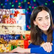 Cheerful brunet portrait at holiday gifts background — Stock Photo #58693799