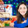 Cheerful brunet portrait at holiday gifts background — Stock Photo #58693801