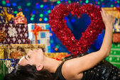 Woman with heart over chest at holiday background — Stok fotoğraf