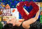 Woman with heart over chest at holiday background — Foto de Stock