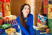 Woman in blue dress at Christmas presents — Stock Photo