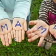 The word mother written in children's hands — Stock Photo #53294203