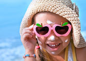 Happy kid with glasses on the nose with sunscreen on your face — Stock Photo
