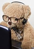 Teddy bear in glasses works behind a computer — Stock Photo