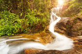 Tropical waterfall in rainforest with sunray — ストック写真
