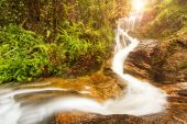 Tropical waterfall in rainforest with sunray — Stock Photo