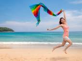 Happy young woman jumping with a colorful scarf on tropical beac — Stock Photo