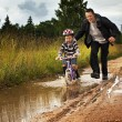 Little boy with Dad on a bike after rain — Stock Photo #78170924