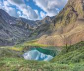 The picturesque lake in a small valley below the mountain peak — Stock Photo