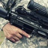 Soldier holding automatic gun — Stock Photo