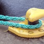 Yellow mooring bollard with green ropes — Stock Photo #68472363