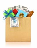 Money and gifts in a paper bag on white background — Stock Photo