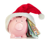 Piggy bank with Santa Claus hat and money on white background — Stock Photo