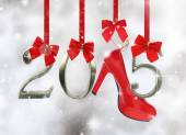 High heel shoe and 2015 number hanging on red ribbons in a glittery background — Stock Photo