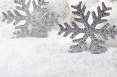 Christmas snowflakes on white snowy background — Stock Photo