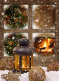 Christmas lantern and ornaments on snow in front of a window — Stock Photo
