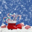 Christmas candy canes in santas boot on snow — Stock Photo #56839833