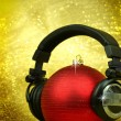 Christmas ball with headphones in glittering background — Stock Photo #59899013