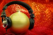 Christmas ball with headphones in glittering background — Stock Photo