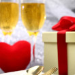 Festive table set with champagne, heart and gift box — Stock Photo #61703237
