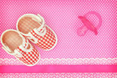 Baby shoes and pink pacifier on polka dots background with copy space — Stock Photo