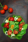 Bowl of fresh colorful salad and tomato cherries on wooden surface — Stock Photo