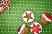 Festive Christmas cupcakes and candy canes on green background — Stock Photo